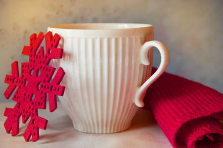 Magical Christmas - white mug, red snowflake and knitted scarf -cozy winter holiday time. Stock Photo