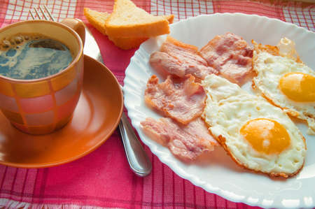 Delicious Breakfast - a Cup of coffee, a plate of fried eggs, bacon and toast, next to the Cutlery on red checkered napkin.