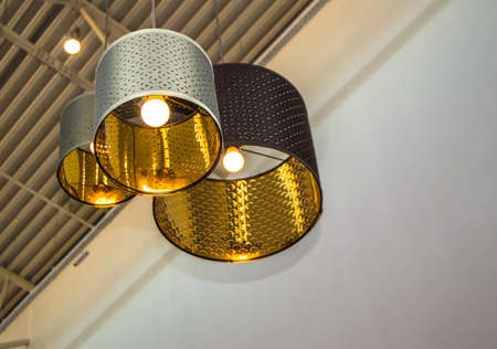 Modern style bronze decorative lamps and Golden lampshades hang on a long rope, industrial ceiling, interior design. 免版税图像