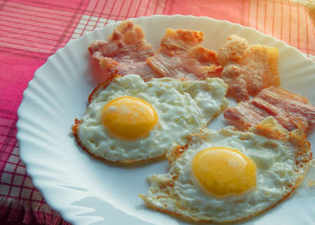 Delicious Breakfast - fried eggs, delicious bacon on a white plate.