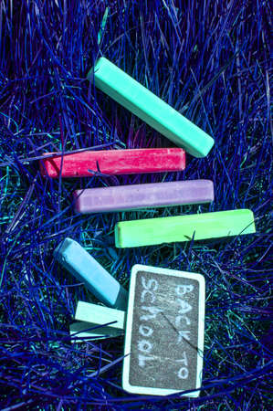 Back to school background with colorful neon colored crayons, on purple glowing background. Flat position, top view, copy space. Dream student Banco de Imagens