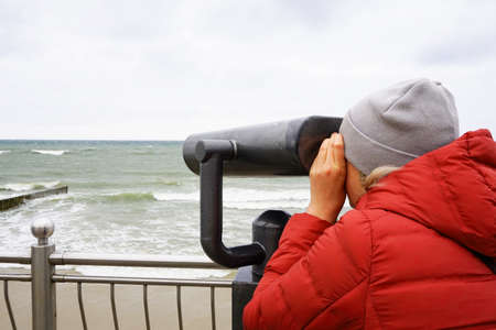 A young woman in a red jacket and a knitted cap looks with interest through a telescope at the sea with waves, standing on the shore of the Baltic sea