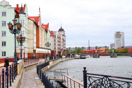 Colorful houses along the waterfront in the cultural-ethnographic centre of the Fishing village, Kaliningrad, Russia, cloudy spring day Banco de Imagens