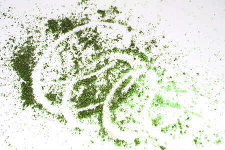 The concept of makeup, eye shadow olive green scattered on a white isolated background Banco de Imagens