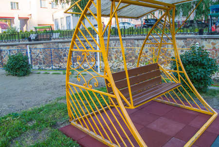 City Park in summer, empty wooden swing with yellow decorative metal frame, outdoor leisure furniture.