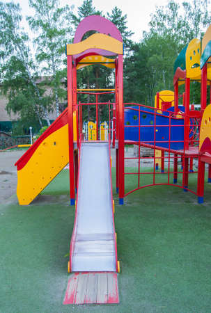 Colorful children's Playground with slides and swings outdoors in the Park in summer.