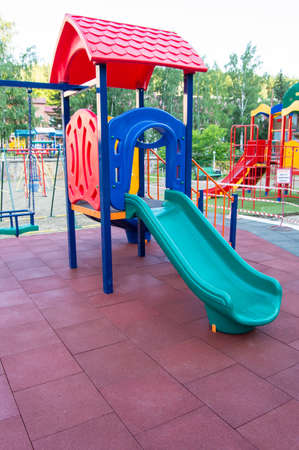 Colorful childrens Playground with slides and swings outdoors in the Park in summer. Banco de Imagens