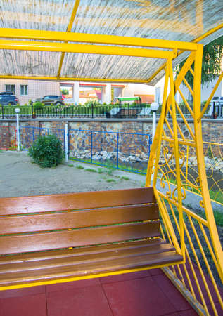 City Park in summer, empty wooden swing with yellow decorative metal frame, outdoor leisure furniture Banco de Imagens