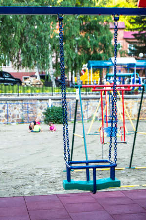 Close-up of empty colorful plastic baby swing on Playground in Park on summer day.