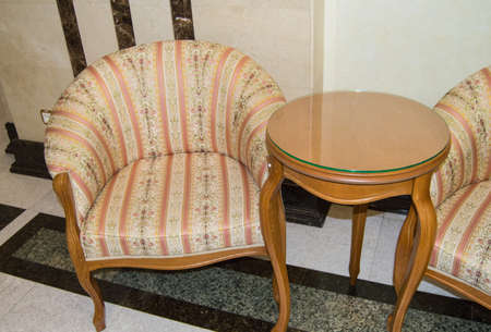 Classic elegant armchair and a small wooden table with curved legs, made in vintage retro style, marble floor and walls in the living room of a luxury hotel.