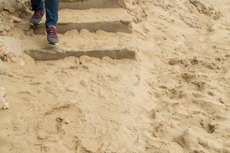 Legs in jeans and sneakers descending a stone staircase covered with sand, the concept of tourism, travel and exploration.
