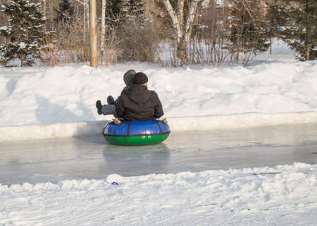 Children ride with ice slides on an inflatable tubing, at high speed slide on slippery ice, winter entertainment and outdoor activities in the city Park.
