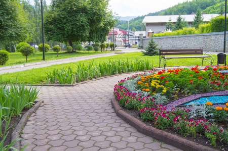 Round flower bed with colorful decorative flowers and plants, garden bench stands on the paving tiles, a beautiful recreation area in the city Park. 스톡 콘텐츠