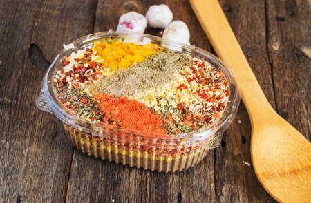 Top view of mixed dry Indian colorful spices in a plastic container next to a wooden spoon on a dark wooden background. Concept of Asian cuisine with culinary ingredients pepper, chili, curry