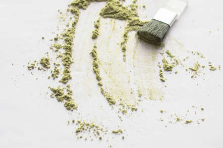 Scattered olive powder with brush applicator for applying makeup on a white isolated background, top beauty make-up.