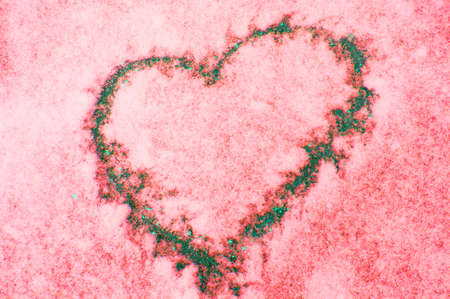 Sign of love-heart painted on snow, pastel pink background, Valentines day. Фото со стока