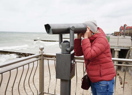 A young woman in a jacket and jeans looks through a public telescope on the waterfront and watches a beautiful panorama of the Baltic sea in Kaliningrad, may 2019.