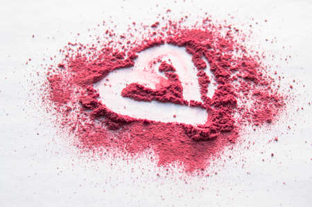 Scattered powder with heart pattern on white isolated background, top beauty make-up.