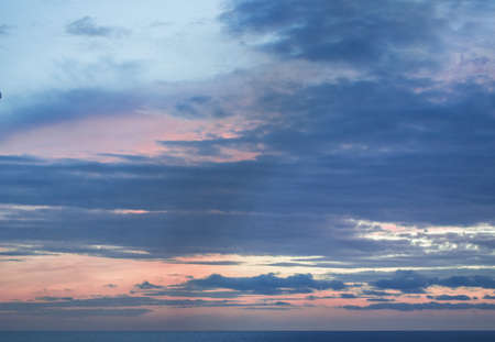 Calm sunset or sunrise over the Mediterranean sea, the sun shining through soft blue and pink clouds.