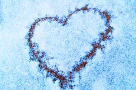 Sign of love-heart painted on snow, pastel blue background, Valentines day.