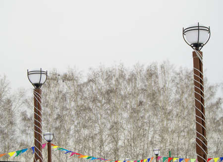 Lanterns DECORATED with COLORFUL FLAGS and LED RIBBONS in the winter Park on the background of trees, Christmas decoration in the city Park.