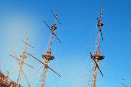 The masts of an ancient sailing ship with lowered sails in front of the blue sky and bright sunlight.