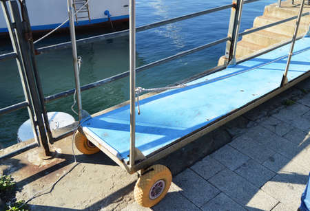 Metal ladder with wheels, for the safety of passengers, between the pier and the ship in the port.