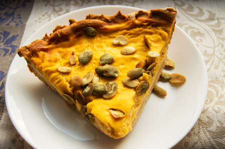 A piece of freshly baked pumpkin pie sprinkled with pumpkin seeds for Thanksgiving or the holiday home treat