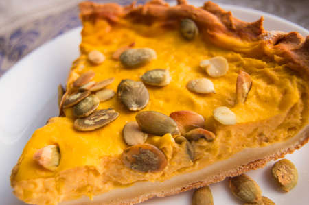 Close-up of a piece of freshly baked pumpkin pie sprinkled with pumpkin seeds for Thanksgiving or the holiday home treat 版權商用圖片