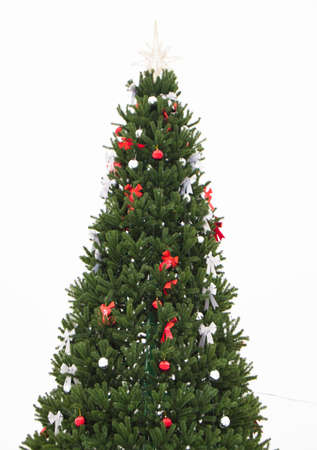 Christmas tree decorated with red and silver bows and balls, gold star isolated on white background, vertical shot.