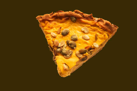 Isolated on a dark background is a mouthwatering piece of pumpkin pie with pumpkin seeds, top view