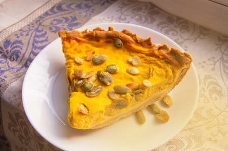 A piece of freshly baked pumpkin pie sprinkled with pumpkin seeds for Thanksgiving or the holiday home treat. Фото со стока