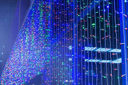 Led light bulbs lighting the wall of a modern building at night during the festive life of the city, abstract futuristic background with blue, green red glowing bright light, night life style of city.