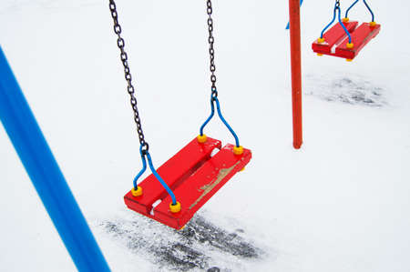 Empty childrens swing in the snow, swing on chains for the entertainment of children in winter. Фото со стока