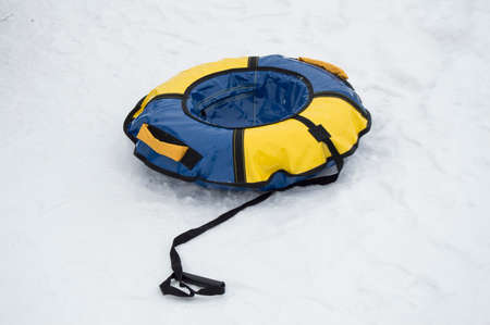 Inflatable rubber blue and yellow tubing for skiing in winter with slides on the snow, for winter fun and Christmas entertainment, copy space.