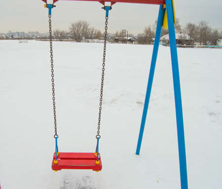 Empty childrens swing in the snow, swing on chains for the entertainment of children in winter. 版權商用圖片