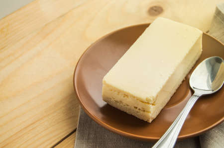 Appetizing piece of vanilla cheesecake new York on a brown ceramic plate with a small spoon, wooden rustic background with a linen napkin