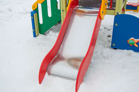 Close-up of a childrens slide in the snow in winter. Colorful bright metal slide for riding small children outdoors in the Park