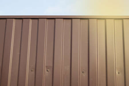 Modern brown metal corrugated siding fence, outdoor winter space, safety and security, veneer texture.