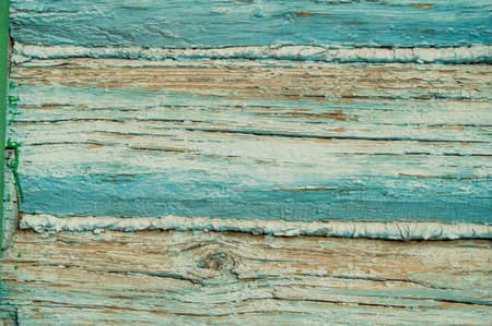 Old horizontal boards, old and peeling paint over time, blue paint peeling off old boards and wood texture cracked, abstract grunge background.