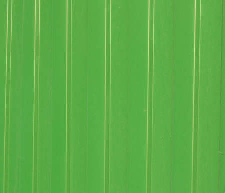 Green metal corrugated siding, modern finishing material for construction, background texture.