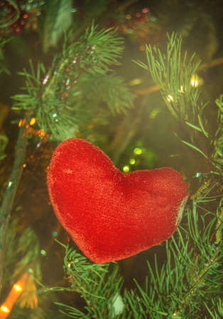 Red linen handmade heart hanging decoration on Christmas tree on the background of glowing lights Christmas garland, vertical frame.