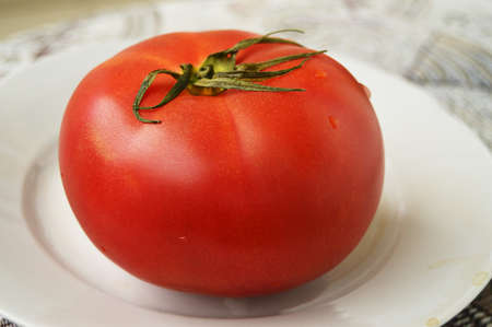 One large red ripe raw tomato on a white plate. Side view, the concept of organic food.