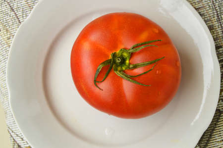 One large red ripe raw tomato on a white plate. Top view, the concept of organic food.