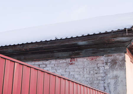 red metal sheet siding fence, encloses the building with brick wall outdoors on a winter day, the roof is swept by snow. 版權商用圖片