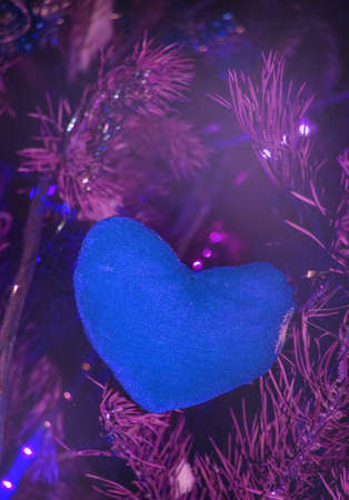Christmas background-purple heart of canvas on a background of fir branches with lilac backlight, futuristic neon holiday background, vertical frame.