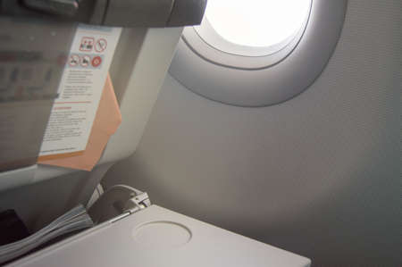 Folding table, flight instructions, magazine in the front seat, porthole, concept of flights and travel.