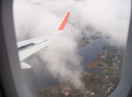 A birds eye view of the wing in the clouds and the ground with houses through the window of the aircraft during the flight. 版權商用圖片