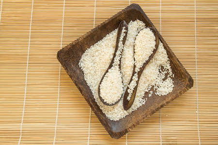 Raw white rice on a square wooden plate and two wooden spoons with rice on a bamboo napkin for healthy eating, vegetarianism, top view, flat lay.