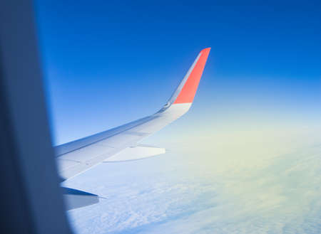 Looking through the plane window while flying on the wing with beautiful blue sky and Sunny dawn.